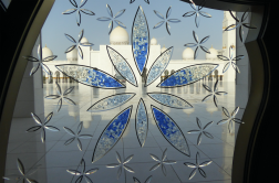 Love this picture of the window glass art with the back of the Zayed Grand Mosque